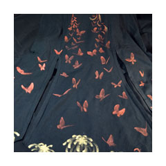 a spreading black skirt painted with copper and gold butterflies and chrysanthemums
